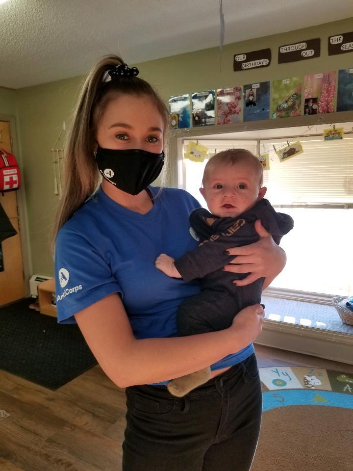 AmeriCorps member holding infant