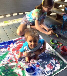 Young boy and sister finger painting